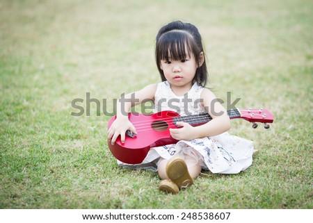 little asian girl play guitar in the garden - stock photo