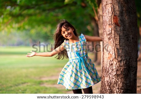 Little asian girl playing near tree in a park - stock photo