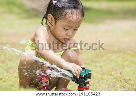 Little asian girl playing with a garden sprinkler. - stock photo