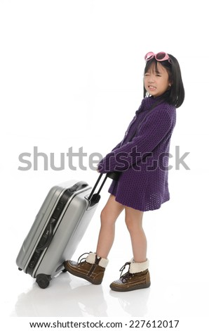 Little asian girl pulling heavy baggage on white background isolated - stock photo