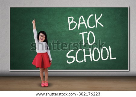 Little asian girl standing in class while raise her hand and celebrate back to school - stock photo