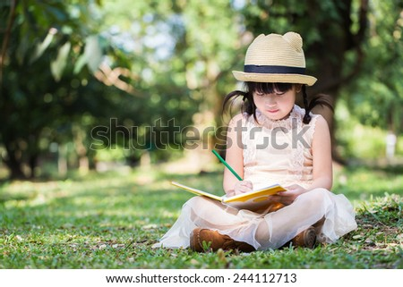 Little asian girl use pencil writting on notebook for writing book with smiling face in the park - stock photo