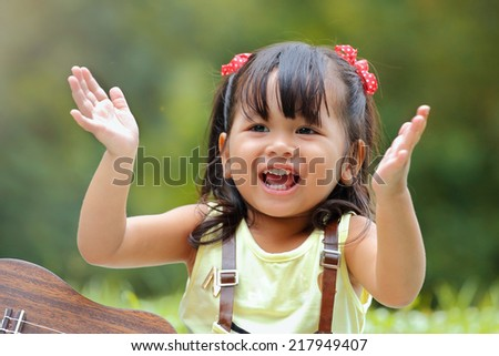 Little asian girl was clapping happily in the park - stock photo