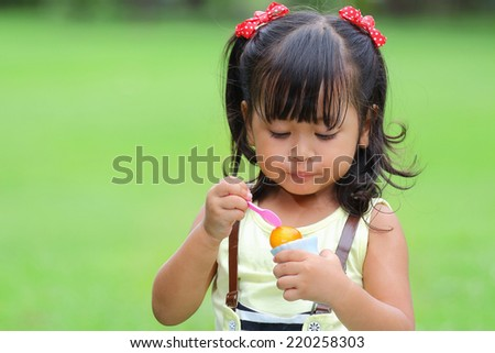 Little asian girl was eating ice cream happily in the park - stock photo