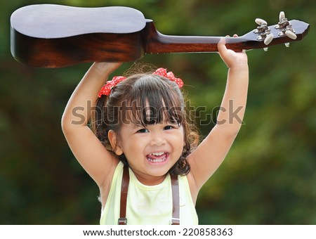 Little asian girl was smile and playing ukulele happily in the park - stock photo