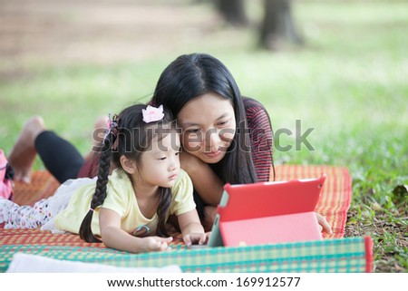 Little Asian girl watching tablet learning and playing tablet - stock photo