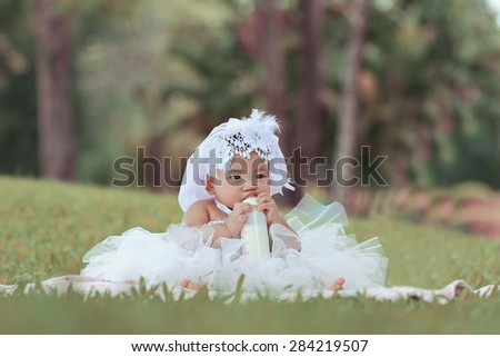 Little asian girl wearing a white dress was playing happily and look at the camera in the park, close up - stock photo