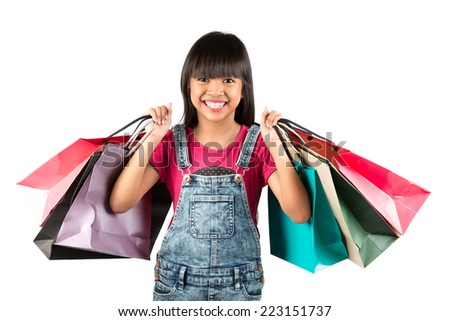 Little asian girl with colorful shopping bags, Isolated over white - stock photo