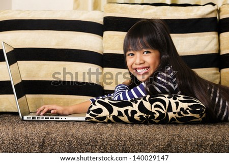 Little asian girl  with computer at home laying on sofa - stock photo