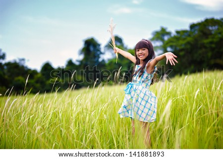 Little asian girl with open arms against green meadow, Outdoor portrait - stock photo