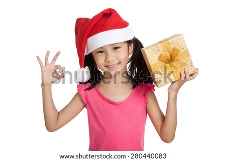 Little asian girl with santa hat and gift box show OK  isolated on white background - stock photo