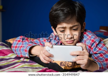 Little Asian kid watching something on a smart-phone - stock photo