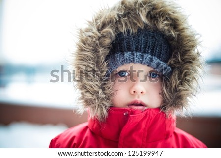 Little baby boy at winter - dressed in warm clothing - stock photo