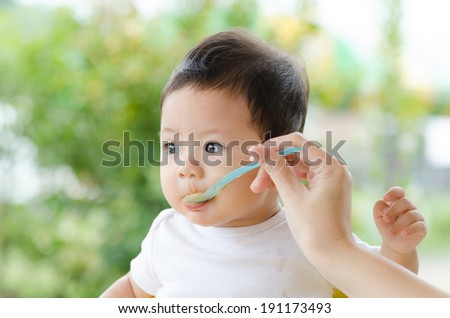 Little Baby Boy Eating in the Park. - stock photo