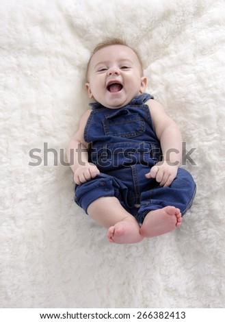little baby boy  having fun lying on his back - stock photo