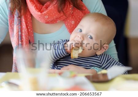 Little baby boy having piece of bread  - stock photo