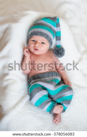 little baby boy in a knitted hat lying on the white bed. - stock photo
