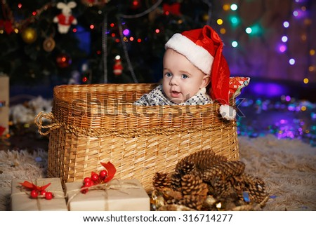 Little Baby Boy in Santa hat sitting in a wicker basket. New Year and Christmas concept - stock photo