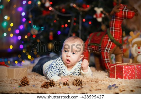 little baby boy lying on his stomach in the room with Christmas decorations - stock photo