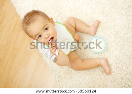 Little baby boy sitting alone on white carpet and eating - stock photo