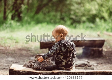 Little baby boy sitting at camping place on wood near campfire. Tent, campfire on campsite outdoors. Travel, camping and adventure with child. Kid sitting at campsite. Cute little traveler. - stock photo