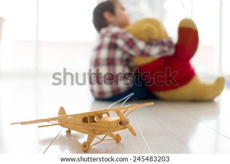 Little baby boy sitting in living room with Teddy bear - stock photo