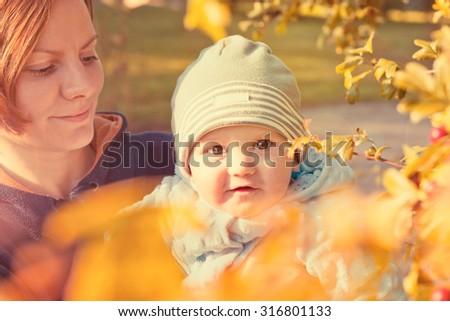 Little baby boy sitting on mother hands and smiling. Vintage style portrait. Warm colors - stock photo