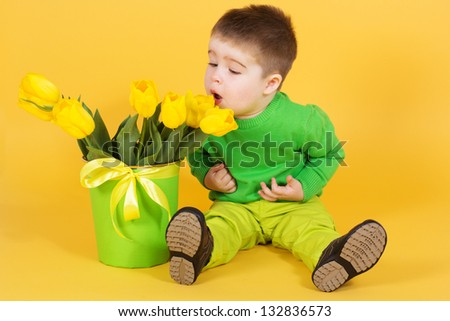 Little baby boy with bouquet of yellow tulips - stock photo