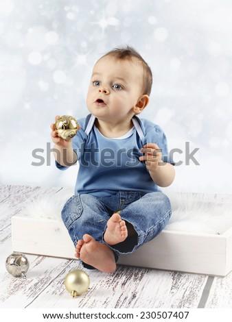 Little baby boy with christmas balls - stock photo