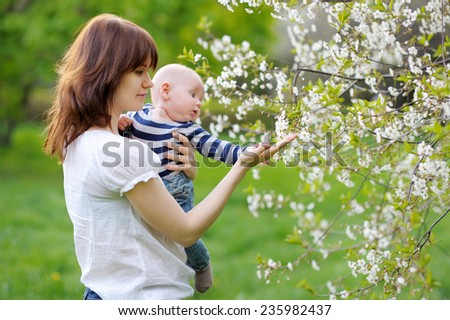 Little baby boy with her young mother in the blossom garden  - stock photo