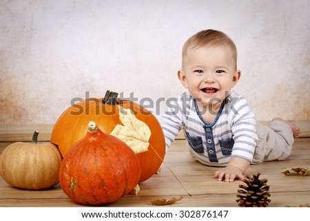 Little baby boy with pumpkins - stock photo