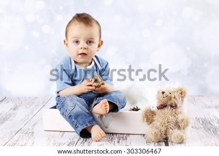 Little baby boy with teddy bear holding christmas ball - stock photo
