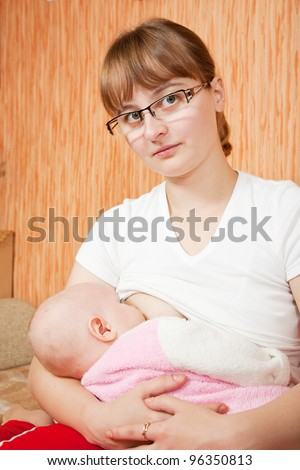 Little baby breast feeding in home interior - stock photo