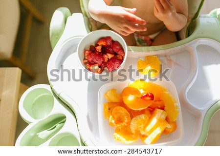 Little baby eating oranges, apricots and strawberries  sitting in the high chair - stock photo