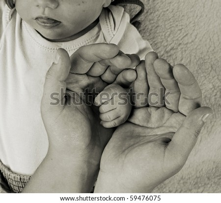 Little baby fingers in mother's hands. Classic monochrome photography. - stock photo