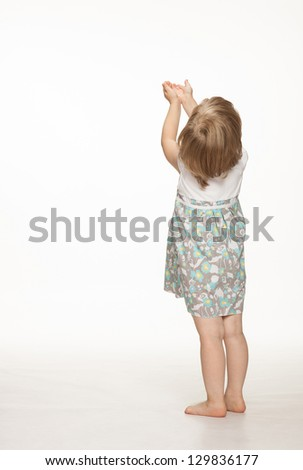 Little baby girl catching something, rear view; white background - stock photo