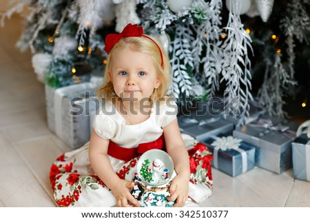 Little baby girl charming blonde in a red dress sitting beside a silver Christmas trees and holding a ball in the interior of the house - stock photo