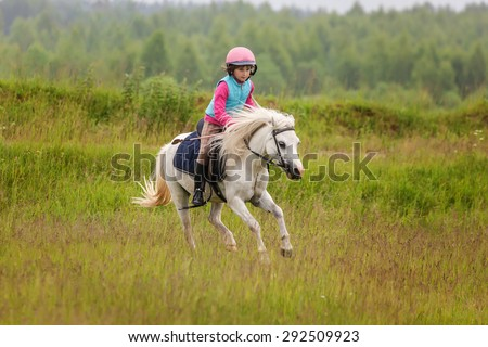 Little baby girl confident riding a horse at a gallop across the field Outdoors - stock photo