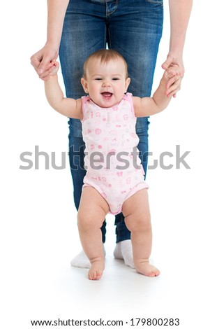 little baby girl doing first steps with help of mom - stock photo