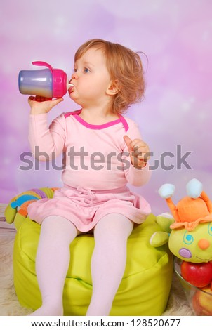 little baby girl drinking an apple juice from bottle  sitting in the room - stock photo