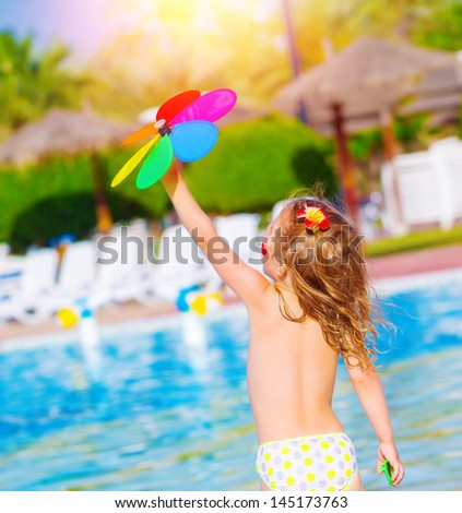 Little baby girl having fun in water park, sweet child play with colorful flower toy, enjoying summer holiday, resting near poolside - stock photo