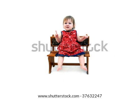 Little baby girl holds a single finger up to illustrate how old she is.  Then frowns in confusion.  She is wearing a red paisley print dress and is barefoot.  All white room. - stock photo
