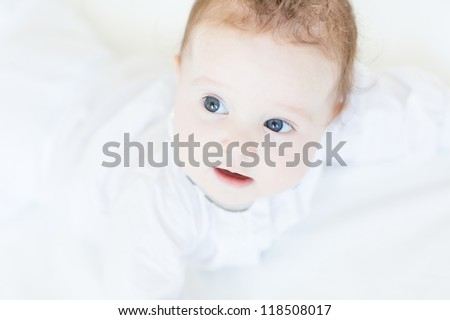 Little baby girl in a white dress lying on her tummy - stock photo