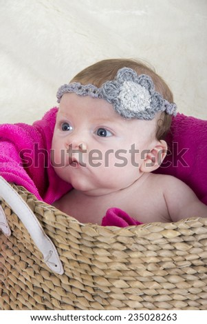 little baby girl in basket with accessory on her head - stock photo
