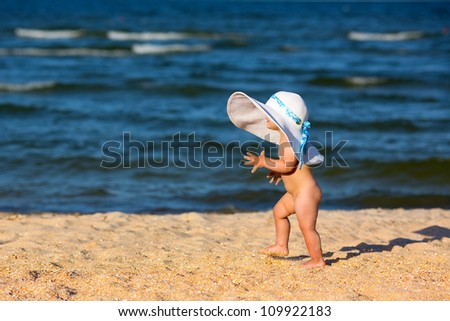 Little baby girl in big hat walking on the beach - stock photo