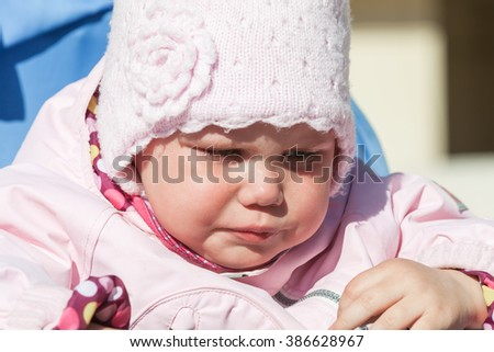 Little baby girl in pink crying, closeup outdoor portrait - stock photo