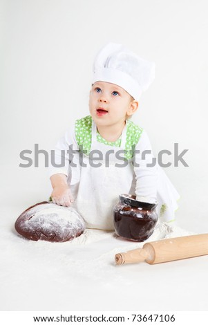 Little baby girl in the cook costume sitting near bread and pot of flour. - stock photo