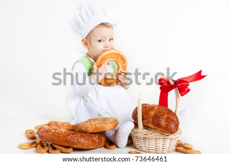 Little baby girl in the cook costume sitting near bread rolls and bagels. She is eating bagel. - stock photo