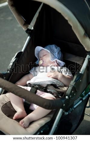 Little baby girl is sleeping in stroller - stock photo