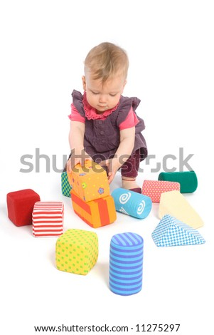 Little baby girl (9 months old) playing with toy blocks. Isolated on white. Toys are property released. - stock photo